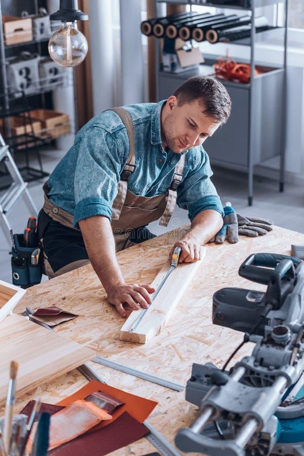 Carpintero moderno que mide el tablón de madera imagen de archivo libre de regalías