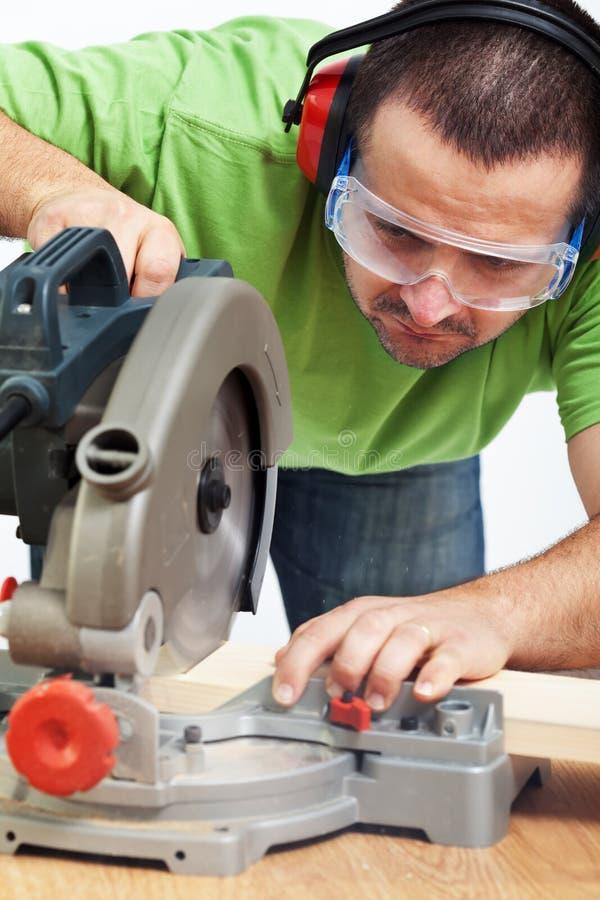 Carpintero o carpintero que trabaja con la herramienta eléctrica imagenes de archivo