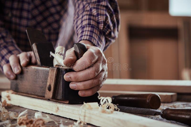 Carpintero o carpintero que acepilla un tablón de la madera imágenes de archivo libres de regalías
