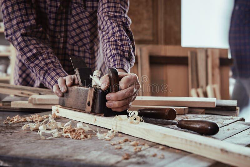 Carpintero o carpintero que usa un viejo avión foto de archivo