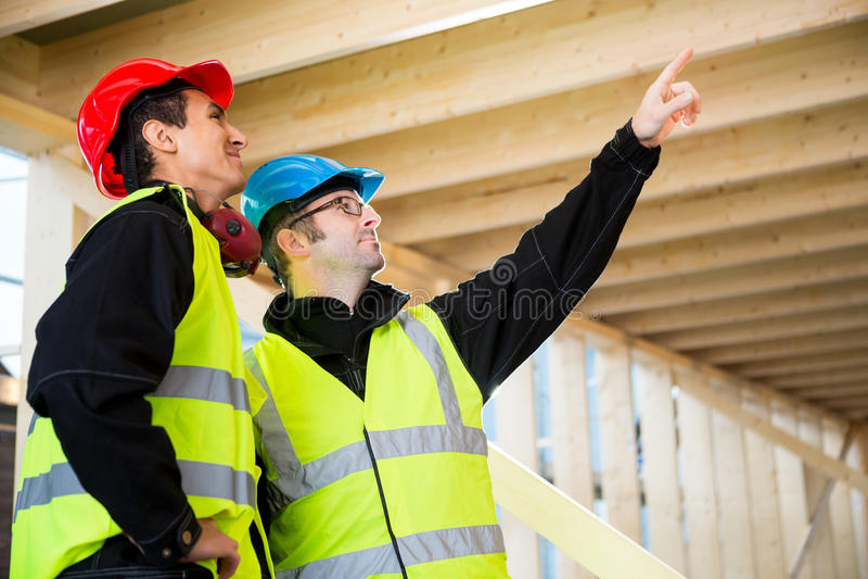 Carpintero Pointing Towards Roof mientras que hace una pausa al colega fotografía de archivo libre de regalías