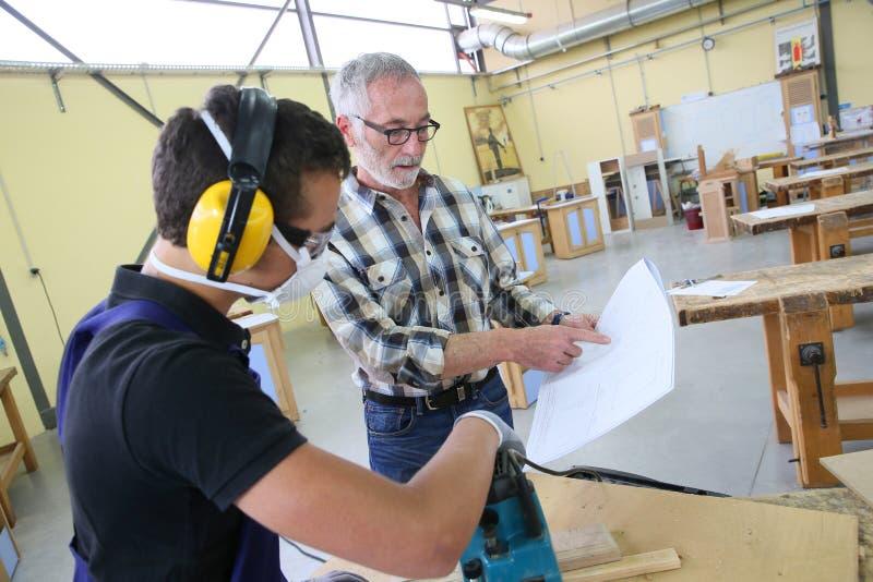 Carpintero profesional con el aprendiz joven fotos de archivo libres de regalías