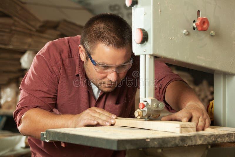 Carpintero profesional que trabaja con la sierra fotografía de archivo