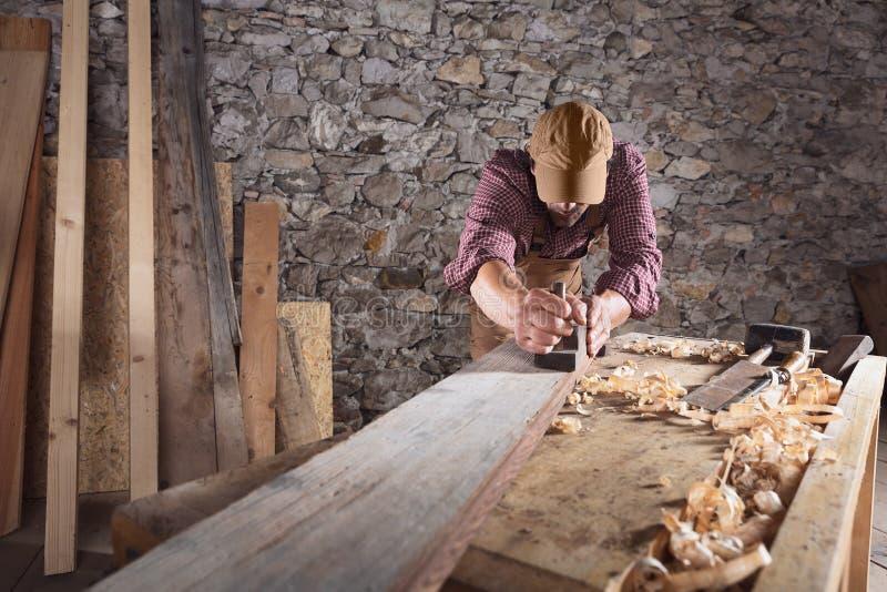Carpintero que allana el haz de madera largo con la herramienta fotografía de archivo