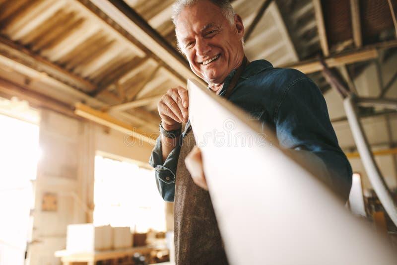 Carpintero que comprueba el tablón de madera fotografía de archivo