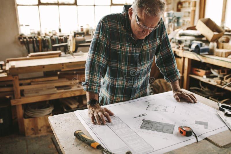 Carpintero que comprueba los planes constructivos antes de comenzar fotografía de archivo libre de regalías
