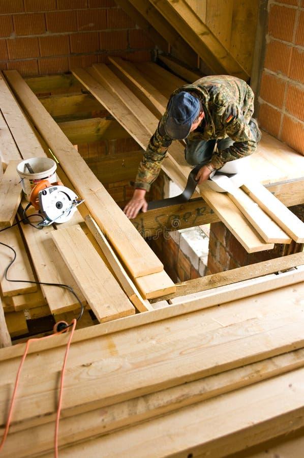 Carpintero que construye el nuevo piso de un cuarto del desván imagenes de archivo