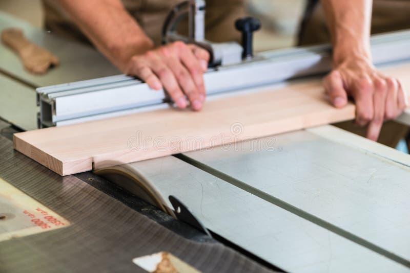 Carpintero que corta al tablero de madera con la sierra circular imagenes de archivo