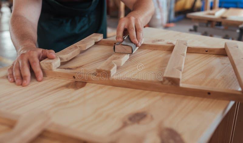 Carpintero que enarena hábilmente un pedazo de madera en su taller imagen de archivo libre de regalías