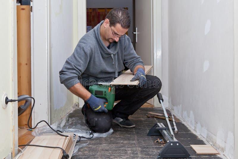Carpintero que enarena y que corta los nuevos tableros de piso imágenes de archivo libres de regalías