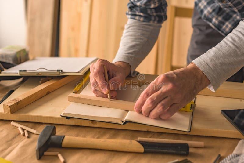 Carpintero que hace el marco en taller fotografía de archivo