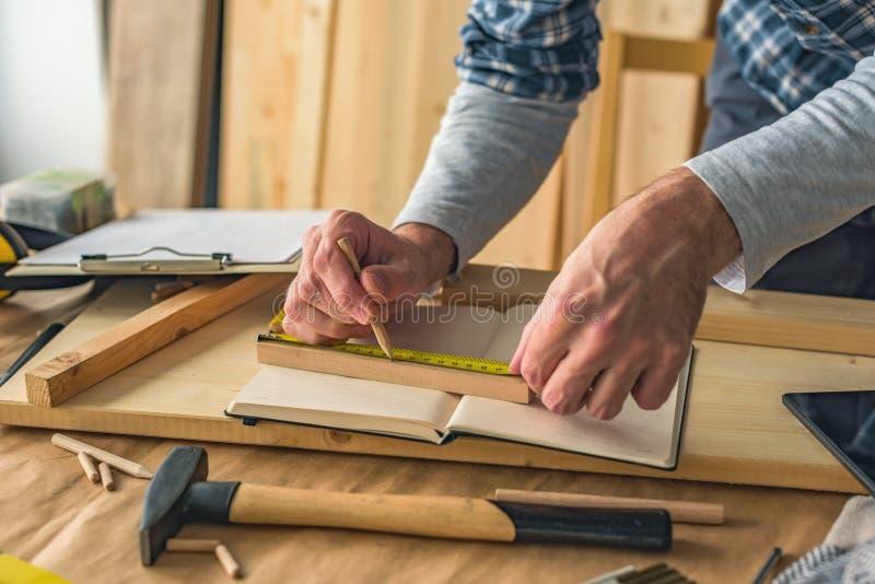Carpintero que hace el marco en taller imagen de archivo