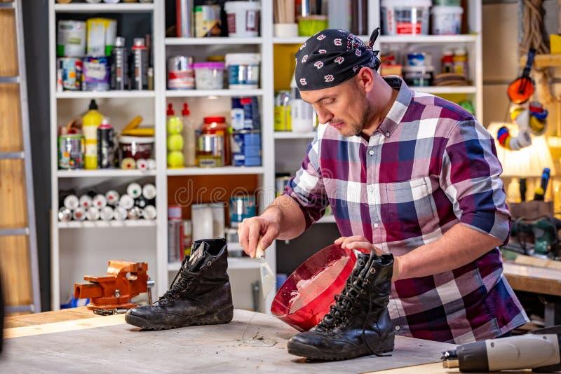 Carpintero que hace su trabajo en taller de la carpintería un hombre en un taller de la carpintería amasa la mezcla del cemento foto de archivo