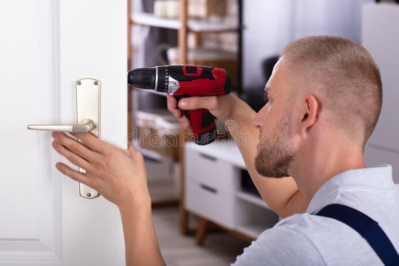 Carpintero que instala la cerradura de puerta imagen de archivo libre de regalías