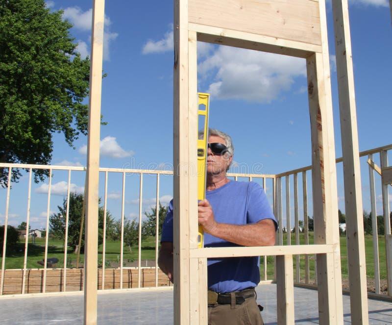 Carpintero que lee un nivel en un marco de la casa imagenes de archivo