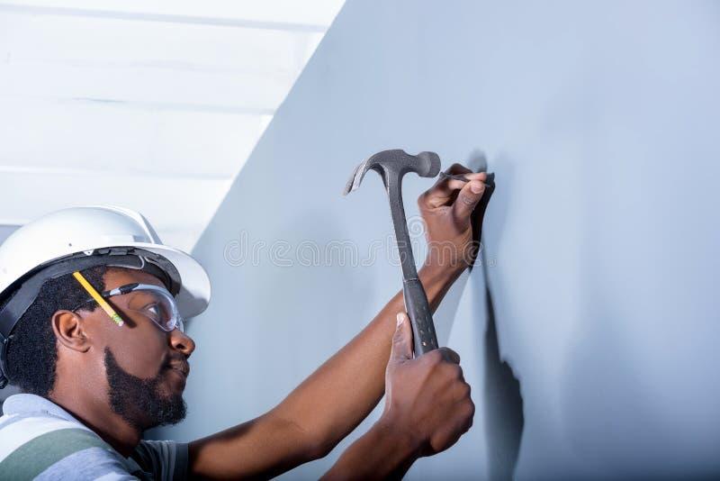 Carpintero que martilla el clavo en la pared imagen de archivo libre de regalías