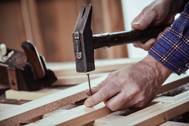 Carpintero que martilla en un clavo con el martillo del vintage fotos de archivo libres de regalías