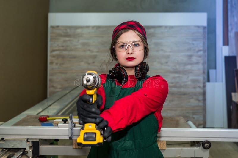 Carpintero que presenta con las máquinas del taladro, carpintero imagen de archivo