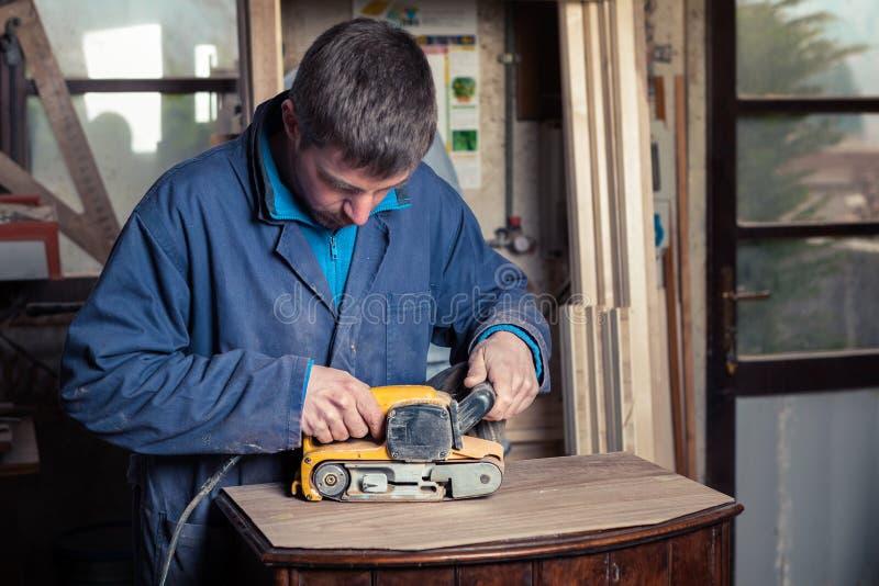 Carpintero que restaura los muebles con la chorreadora de la correa imágenes de archivo libres de regalías