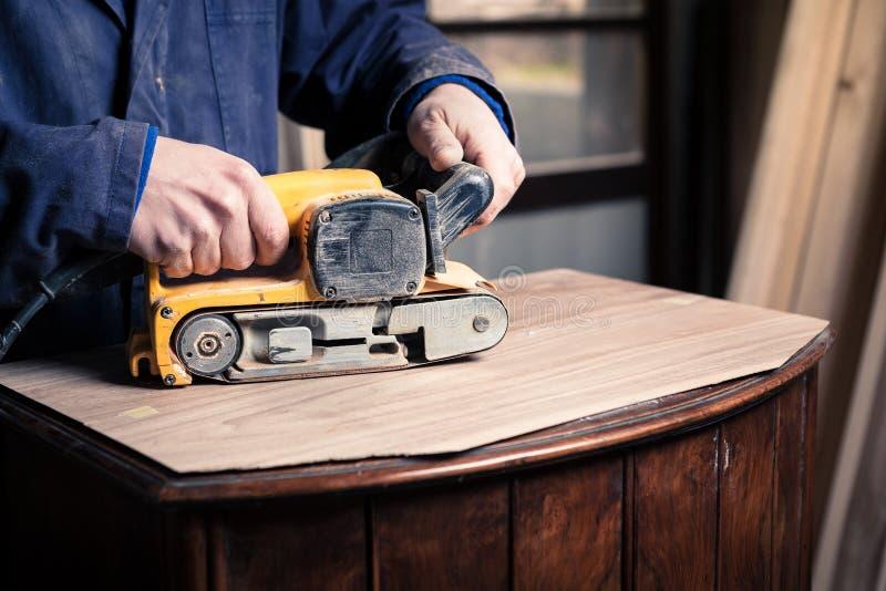 Carpintero que restaura los muebles con la chorreadora de la correa foto de archivo