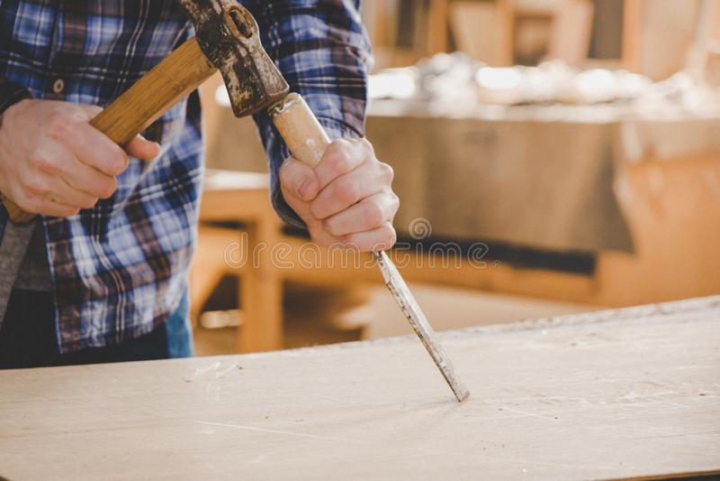 Carpintero que trabaja con el cincel y el martillo en la madera Fondo del taller fotografía de archivo libre de regalías