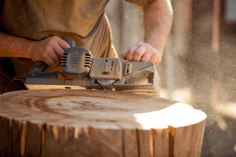 Carpintero que trabaja con la alisadora eléctrica en tocón de madera al aire libre imagen de archivo