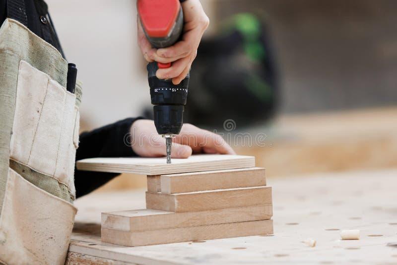 Carpintero que trabaja con un destornillador el?ctrico en el banco de trabajo imagenes de archivo