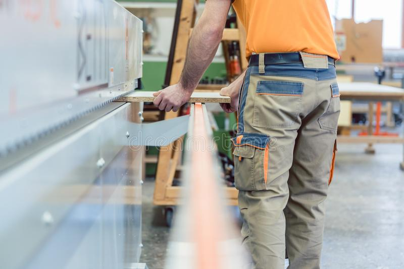 Carpintero que trabaja en fábrica de los muebles en la máquina imagen de archivo