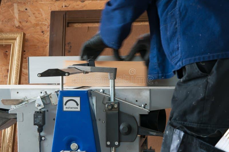 Carpintero que trabaja en la alisadora de madera foto de archivo
