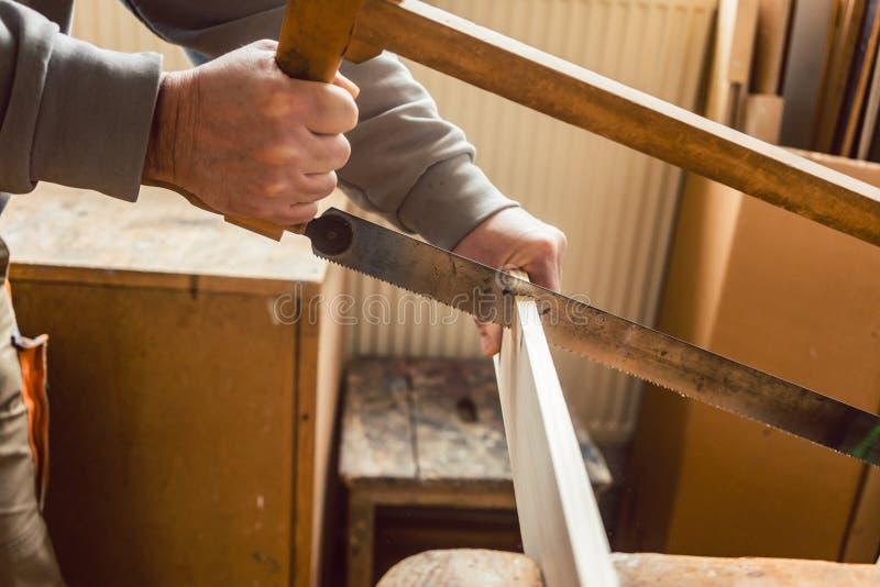 Carpintero que trabaja en la madera con la sierra del marco fotografía de archivo