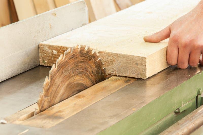 Carpintero que trabaja en las máquinas de la carpintería en departamento de la carpintería fotografía de archivo