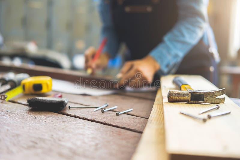 Carpintero que trabaja en las máquinas de la carpintería en tienda de la carpintería Mañana fotos de archivo