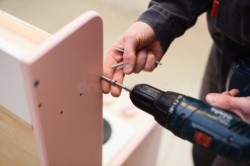 Carpintero que trabaja en los muebles del juego Ajuste de los tornillos con destornillador imagenes de archivo