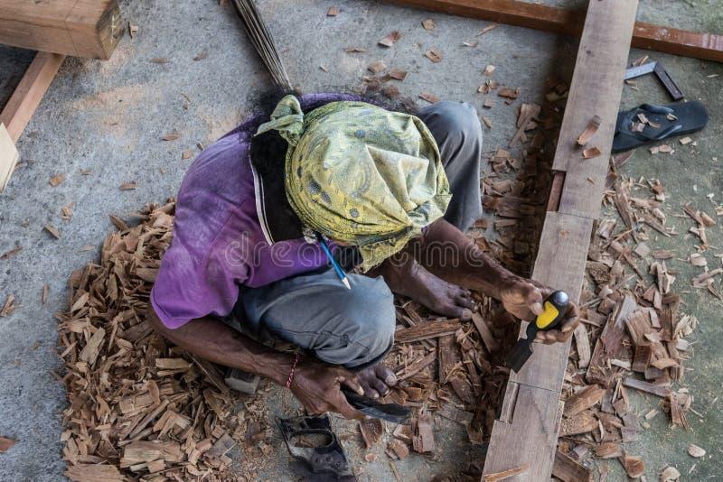 Carpintero que trabaja en tienda manual tradicional de la carpintería en un país del tercer mundo foto de archivo