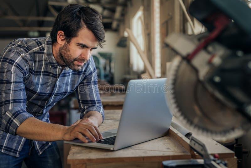 Carpintero que trabaja en un ordenador portátil en su estudio de la carpintería fotos de archivo