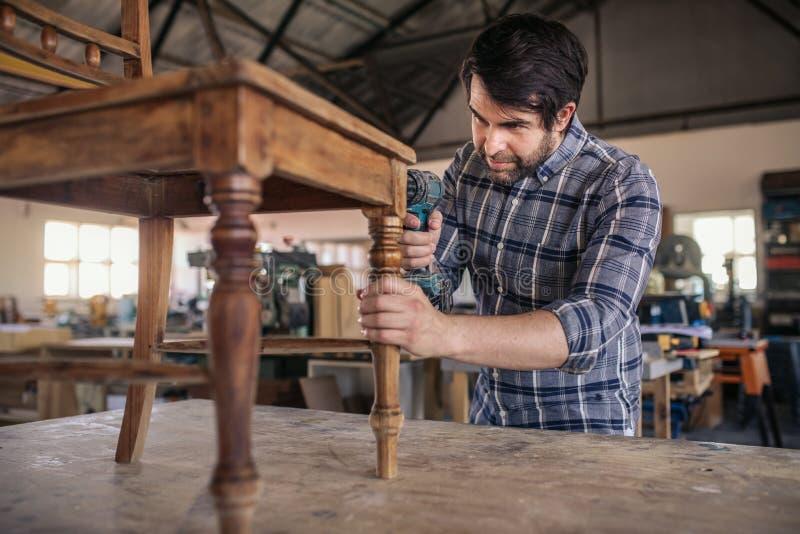 Carpintero que une con tornillos una silla en su taller de la carpintería foto de archivo