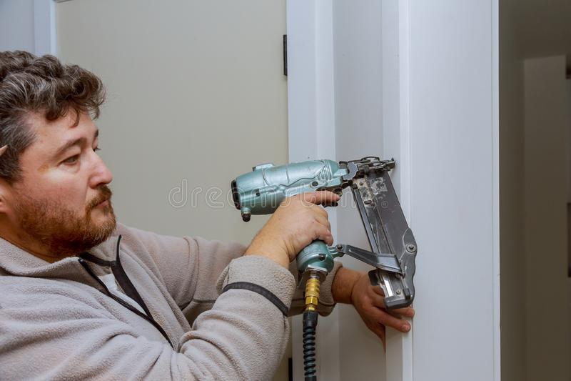 Carpintero que usa el arma del clavo a los moldeados en la puerta, ajuste que enmarca foto de archivo libre de regalías