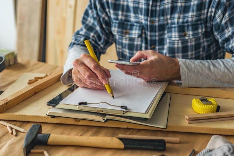 Carpintero que usa el tel?fono elegante para terminar proyecto para hacer la lista foto de archivo libre de regalías