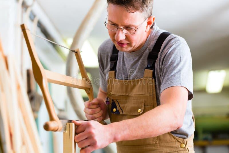 Carpintero que usa la sierra de la mano fotos de archivo
