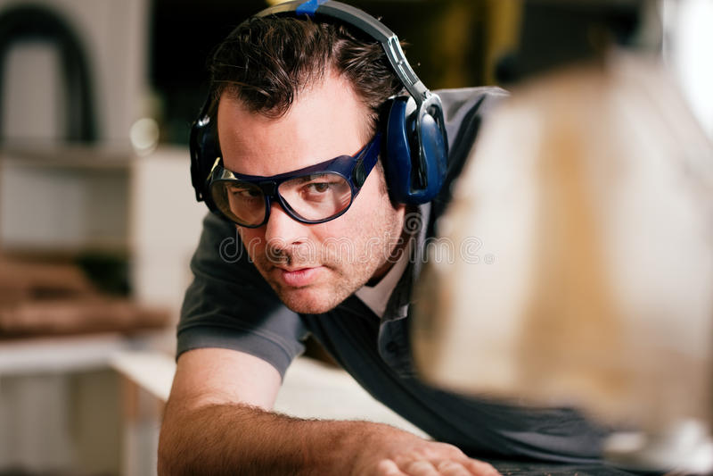 Carpintero que usa la sierra eléctrica imagenes de archivo