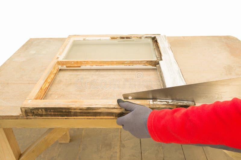 Carpintero que usa un handsaw para la renovación de un marco de ventana viejo imágenes de archivo libres de regalías