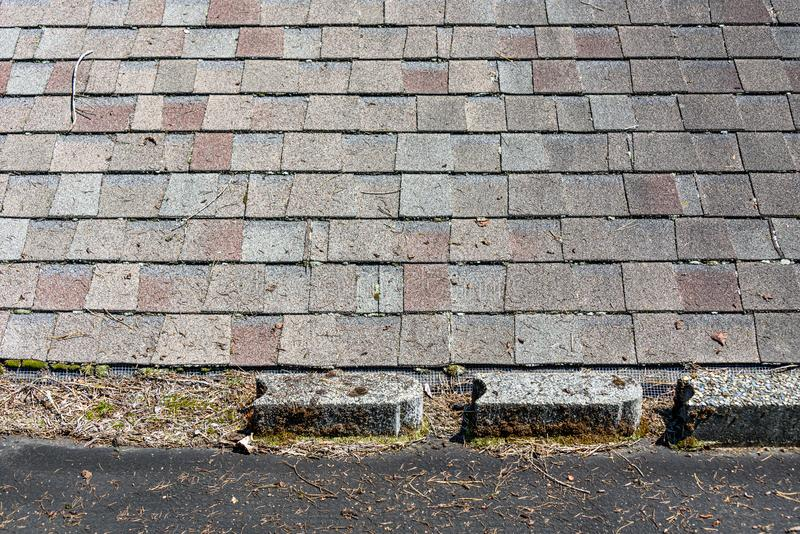 Carport torch down black roofing material covered in tree debris, cement blocks, and moss, connected to house roof with asphalt sh. Ingles royalty free stock photo