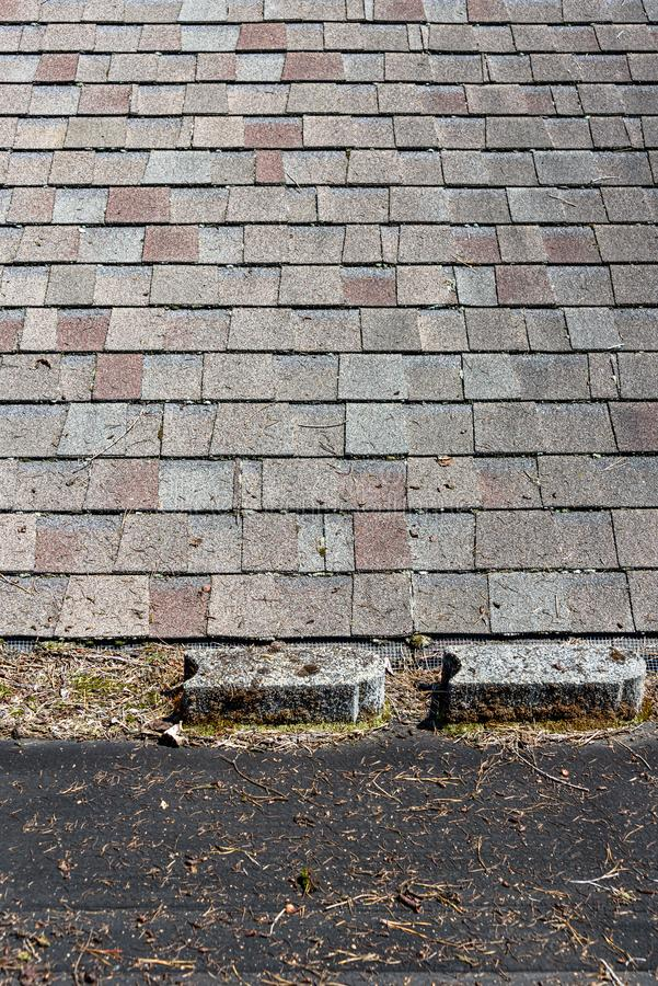 Carport torch down black roofing material covered in tree debris, cement blocks, and moss, connected to house roof with asphalt sh. Ingles stock image