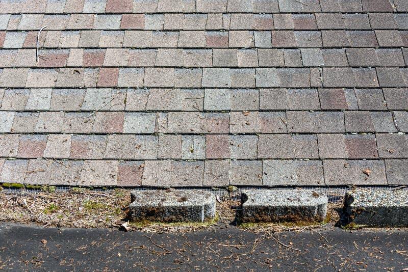 Carportfackla ner svart taklägga material som täckas i trädskräp, cementkvarter och mossa, förbindelse för att inhysa taket med s royaltyfri foto