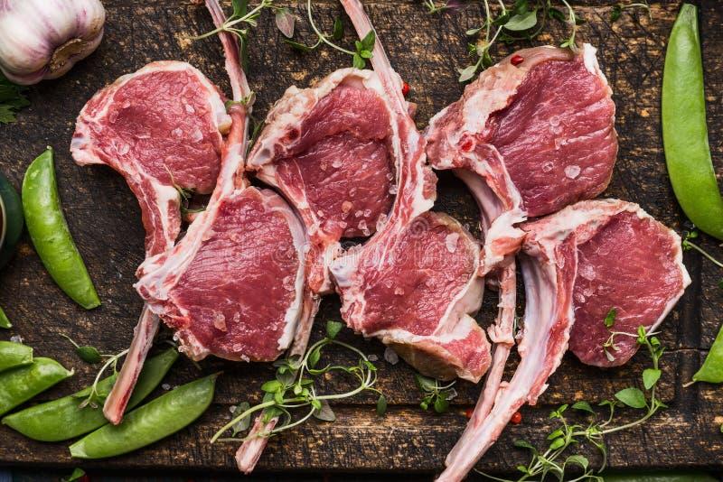 Carrè di agnello della carne cruda e pisello su fondo di legno scuro, vista superiore fotografia stock libera da diritti