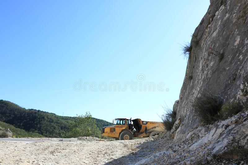 A dumper truck used in a Carrara marble quarry. Large yellow dum stock image