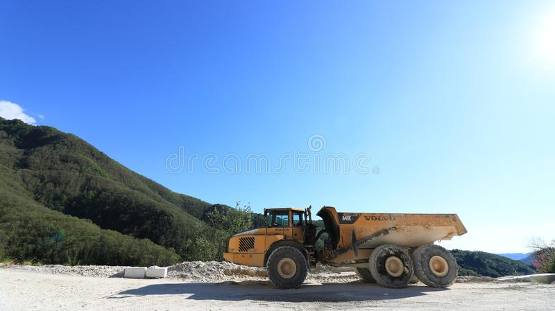 A dumper truck used in a Carrara marble quarry. Large yellow dum stock photography