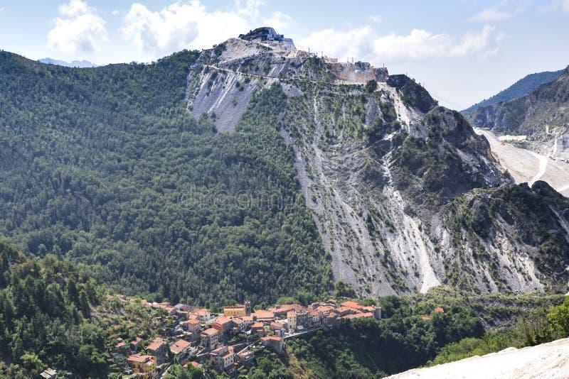 Carrara marmorvillebråd Sikt på de Apuan fjällängarna och byn av arkivfoton