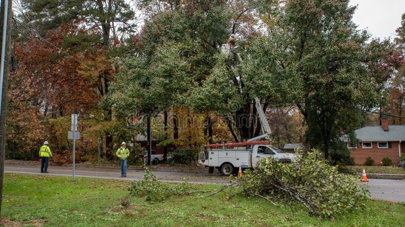Carrboro, βόρεια Καρολίνα, ΗΠΑ 13 Νοεμβρίου 2018: Οι εργαζόμενοι που επισκευάζουν τα ηλεκτροφόρα καλώδια μετά από το δέντρο αφόρη στοκ εικόνα με δικαίωμα ελεύθερης χρήσης