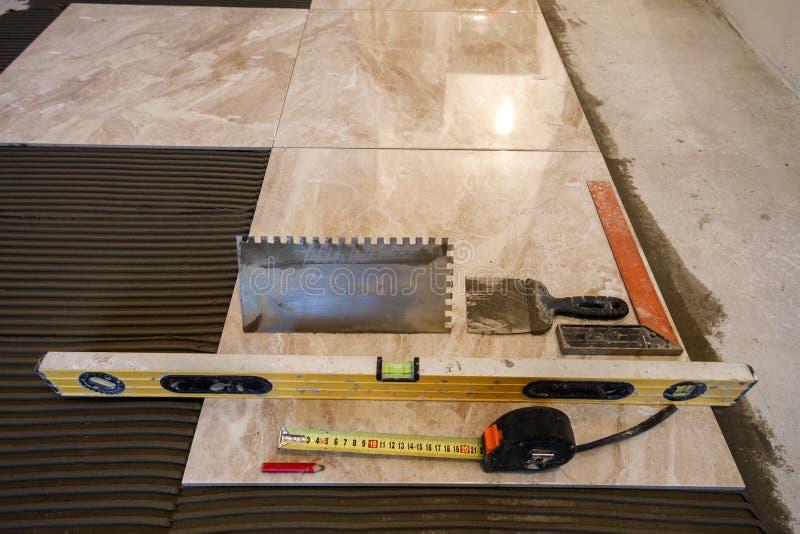 Carreaux de céramique et outils pour le carreleur Installation de carrelages Hom photos stock